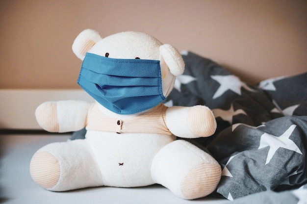 Selective focus shot of a white stuffed teddy bear with a mask