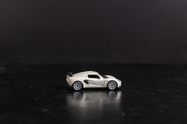Selective focus shot of a white toy sports car on a black surface