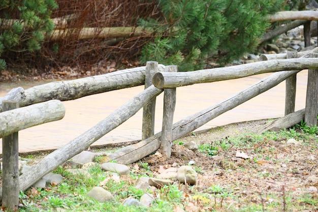 Colpo di messa a fuoco selettiva di una staccionata in legno vicino a un sentiero nel parco