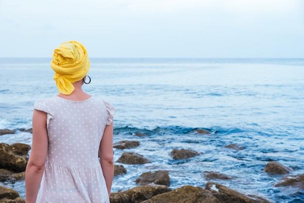 Messa a fuoco selettiva di una giovane donna che si rilassa in riva al mare