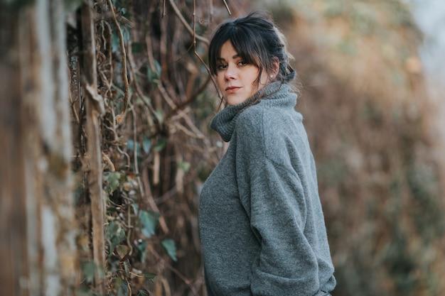 Messa a fuoco selettiva di una giovane donna che indossa un maglione a collo alto grigio