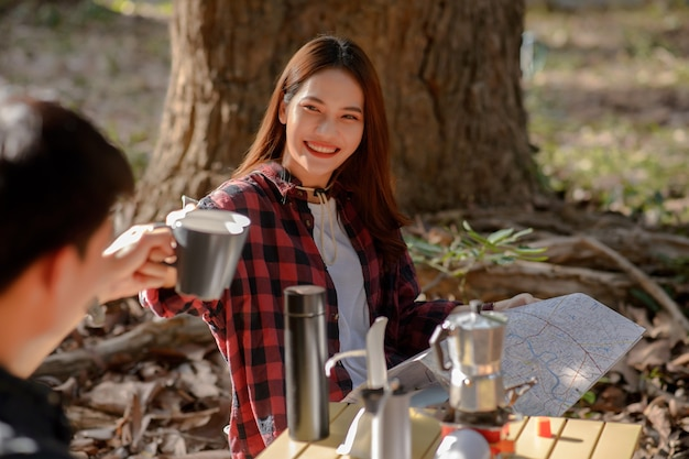 Selective focus at smiley woman, young couple clinking coffee mugs with happy together in the morning in front of a camping tent in the morning at nature park