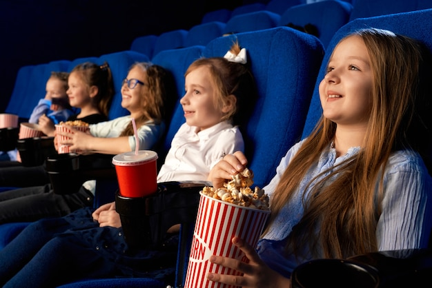 Selective focus of smiling little girl holding popcorn bucket, sitting with laughing friends in comfortable chairs in cinema. children watching cartoon or movie, enjoying time