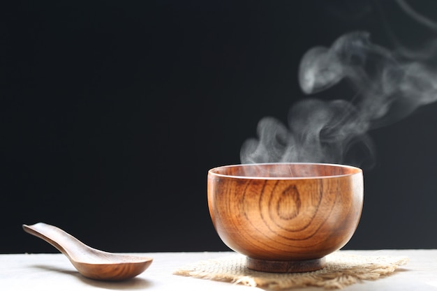 Selective focus of smoke rising with hot soup in cup on dark background.