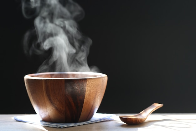 Selective focus of smoke rising with hot soup in cup