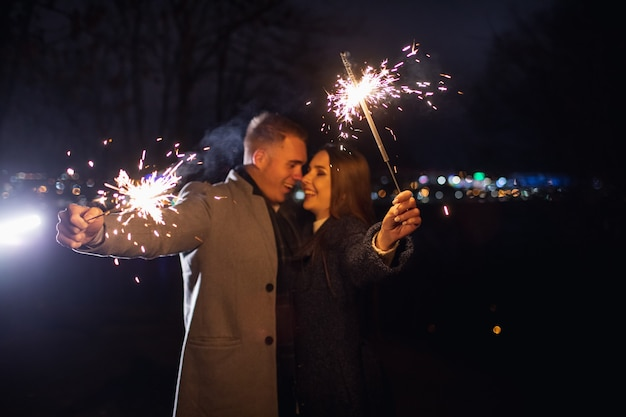 Selective focus of sparklers in hands of young couple enjoying holiday time outdoors.
