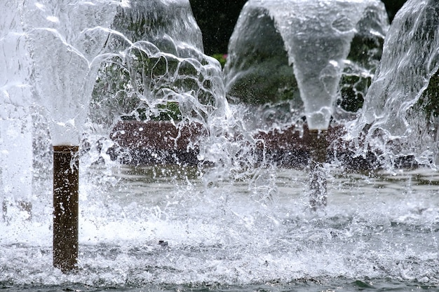 Selective focus on spray of urban fountain and blurred background copy space