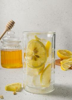 Selective focus, a tall glass of lemon iced tea with a jar of honey on a light background