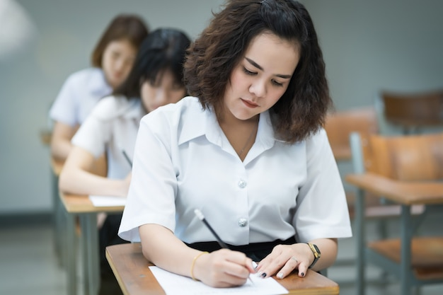 Selective focus of the teen college students sitting on lecture chair in classroom write on examination paper answer sheet in doing the final examination test. female students in the student uniform.