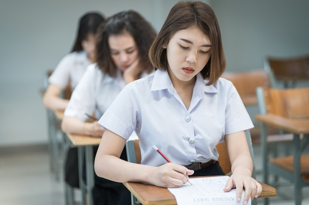Selective focus of teenage college students sit on lecture chaire, write on examination paper answer sheet taking final examination room or classroom. university students in uniform in classroom.