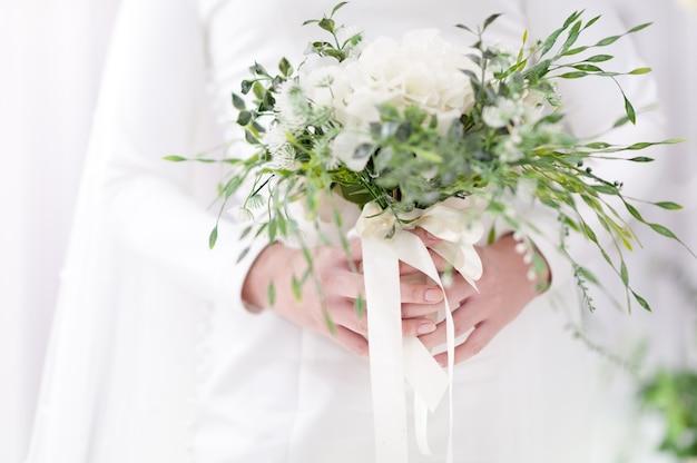 선택적 포커스 결혼식 꽃다발을 들고 신부의 손 흰색과 녹색 톤입니다. 행복한 하루의 우아한 단순함.