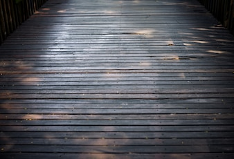 Selective focus the old hard wood floor of the bridge with grungy texture background.