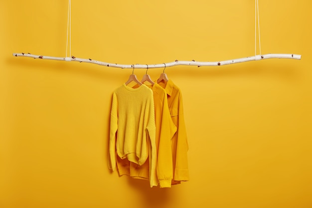 Selective focus. three items of clothes on hangers. long sleeved yellow jumpers on wooden rack near bright vivid wall.