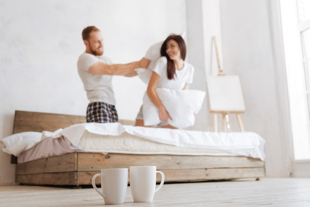 Selective focus on two cups and a radiant young couple beating each other with pillows in bed behind