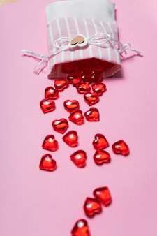 Selective focus. valentine's day card. glass red hearts scattered from a beautiful cloth bag. the view from the top. pink background