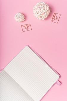 セレクティブフォーカス。バレンタインデーのレイアウト。コピースペース付きのピンクのメモ帳。ひな形とピンクの紙の背景に。上からの眺め