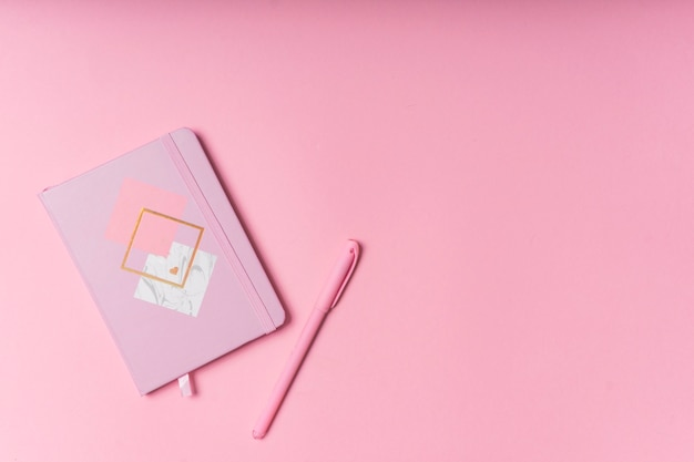 Selective focus. valentine's day layout. pink notepad with copyspace. on a pink paper background with stationery. the view from the top