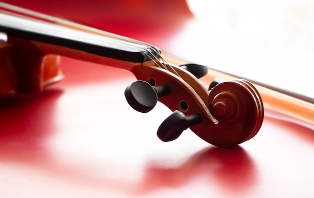In selective focus of the  violin scroll put on red surface