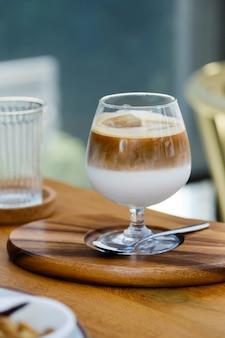 선택적 초점, 아이스 커피 두 레이어 신선한 우유와 에스프레소 카페에서 나무 테이블에 짧은 와인 잔.