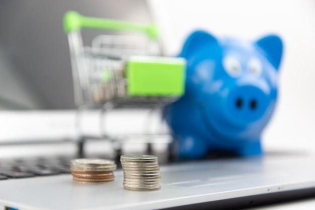 ぼやけたショッピングカートと貯金箱とラップトップの背景にコインパイルとセレクティブフォーカス。オンラインショッピング、投資の節約、購入、ビジネスコンセプト。