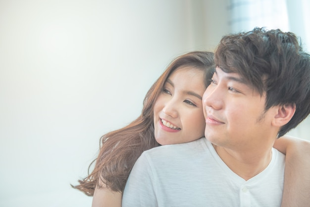 Selective focus on woman face with portrait of young asian couple girl piggyback man from back on bed,romantic asia people in love hugging while sitting in bed,valentine day concept with copy space.