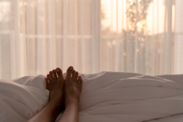 Selective focus of woman feet relax on white blanket in bedroom in the morning with warm sun light from window