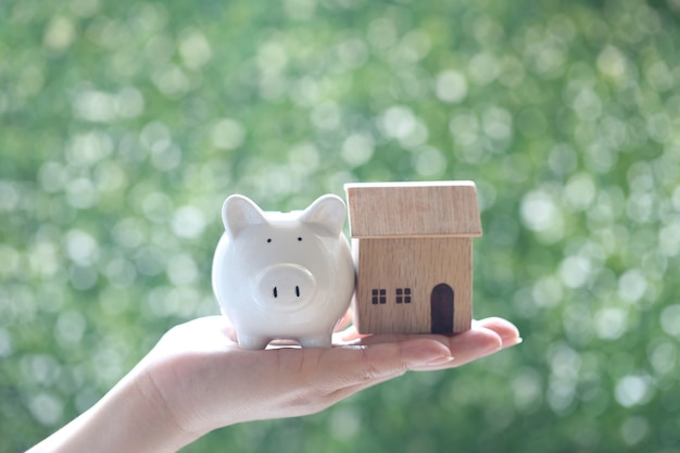 Selective focus of woman hand holding piggy with model house on natural green background, business investment and real estate concept