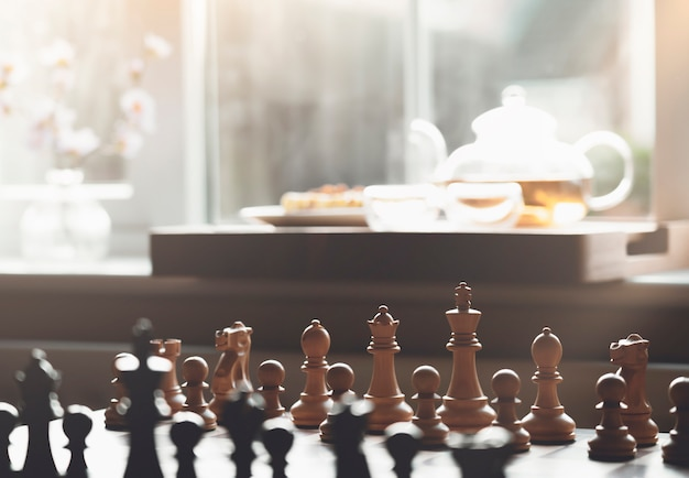 Selective focus of wood chess pieces on board game with blurry tea pot next to window