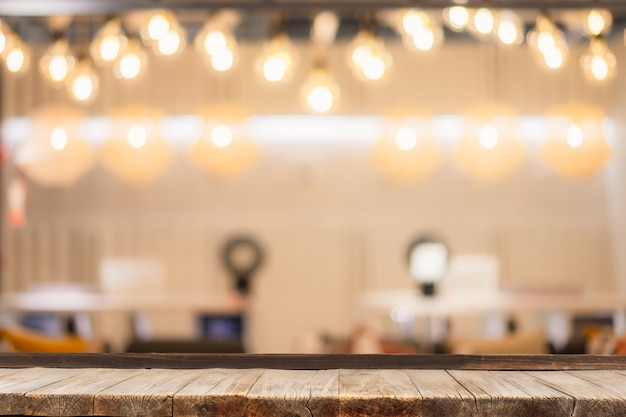 Selective focus of wooden table in front of decorative indoor string lights. Premium Photo