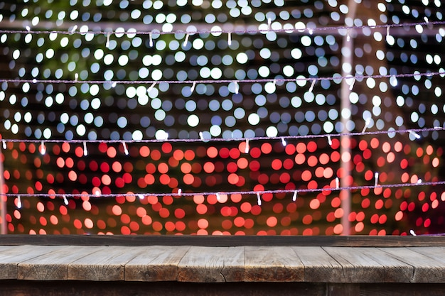 Selective focus of wooden table in front of decorative indoor string lights.