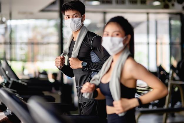 マスクの選択的な焦点の若い男、スポーツウェアとスマートウォッチを身に着けている前景のぼやけた若いセクシーな女性、彼らは現代のジムでのトレーニングのためにトレッドミルで走っています、