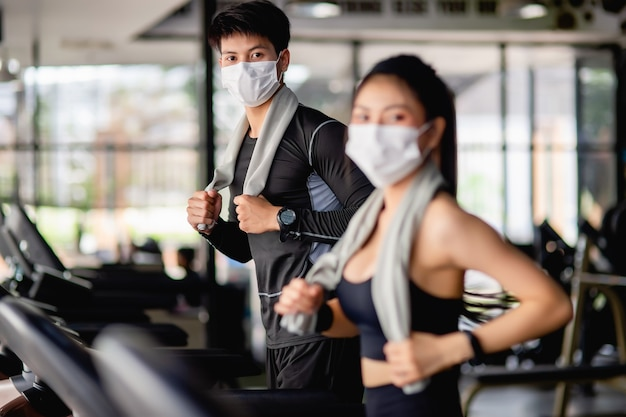Selective focus young man in mask, blurred young sexy woman in foreground wearing sportswear and smartwatch, they are running on treadmill to for workout in modern gym,
