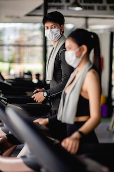 Selective focus young man in mask, blurred young sexy woman in foreground wearing sportswear and smartwatch, they are standing setting program on treadmill to for workout in modern gym, copy space