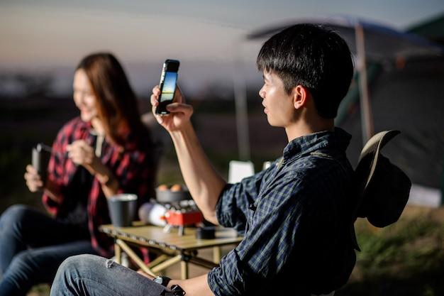 선택적 초점, 젊은 남자는 여자 친구와 캠핑 여행 중에 스마트폰을 사용하여 자연 사진을 찍고, 여름 방학에 텐트 앞에 앉아 행복한 미소를 짓습니다.