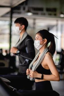 Messa a fuoco selettiva, giovane donna sexy in maschera che indossa abbigliamento sportivo e smartwatch e giovane sfocato, stanno correndo sul tapis roulant per allenarsi in palestra moderna, copia spazio