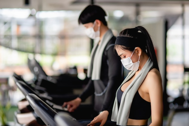 Selective focus,  young sexy woman wearing sportswear and smartwatch and blurred young man they are standing setting program on treadmill to for workout in modern gym, copy space