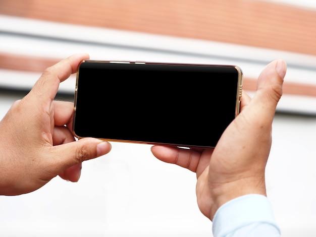 빈 검은 화면이 있는 휴대폰을 들고 선택적으로 집중된 손, 정보 검색, 사람들과의 연결, 온라인 학습