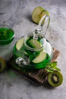 Селективный фокус свежесваренный зеленый чай с киви и мятой в прозрачном чайнике с фруктами и фруктами ...
