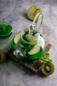 Selective focusfreshly brewed green tea with kiwi and mint in a transparent teapot with fruits and f...