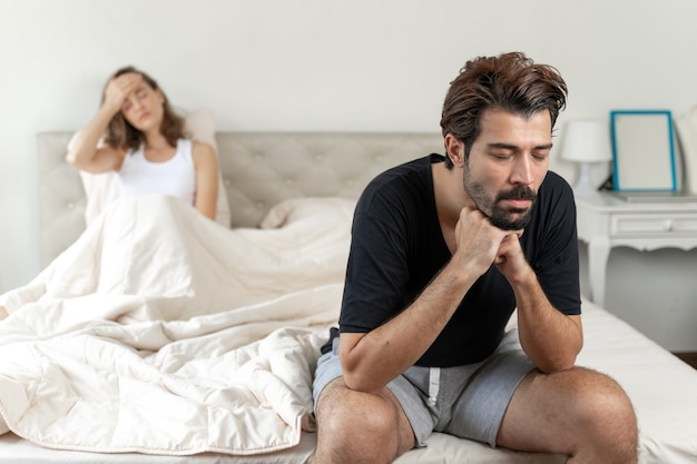 Selective husband sitting on bed with feel bored about her wife