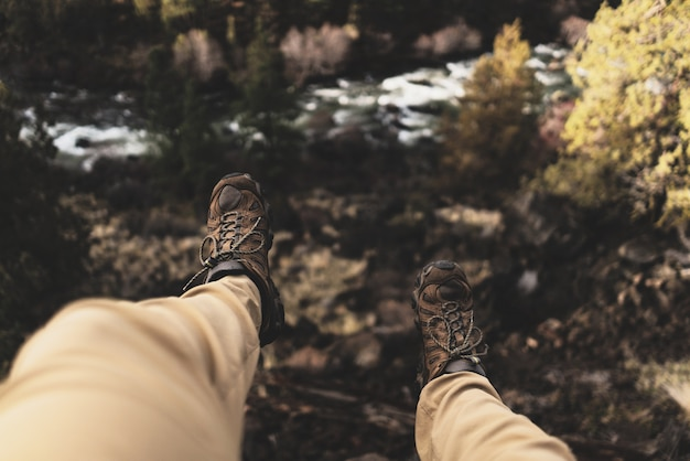 Selective overhead shot of a person wearing brown hiking sport shoes sitting on a cliff near trees
