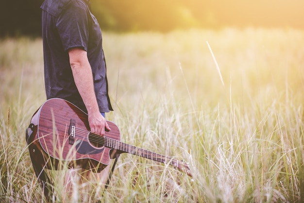 Selective shot of a person holding a brown acoustic guitar standing in the middle of grass field