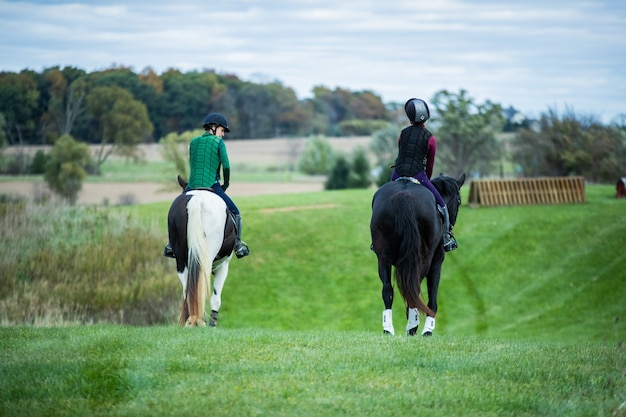 Selective shot of two people wearing horse riding vests riding on horses with black and white tails