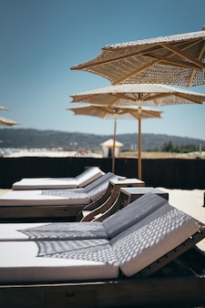 Selective vertical shot of white loungers under parasols by the beach