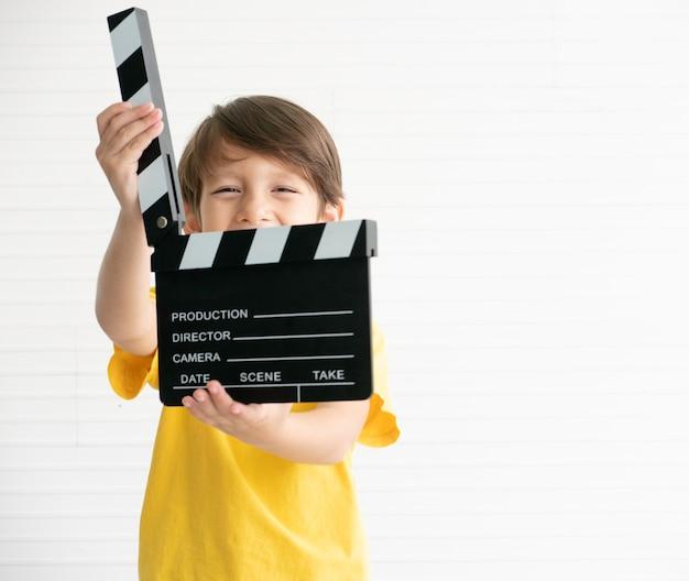幸せな少年が保持している選択フォーカスフィルム製作クラッパーボード