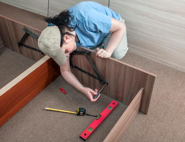 집에서 자기 조립 가구, 조립하는 여성 주부가 침대 프레임을 조립합니다.