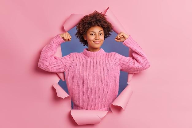 La bella giovane donna afroamericana sicura di sé alza le braccia mostra che i bicipiti sono forti e potenti