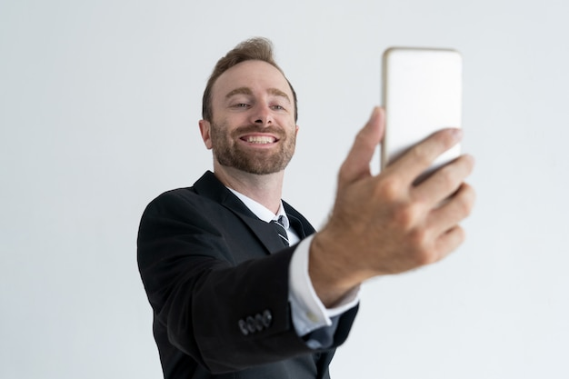 Self-assured business man posing and taking selfie photo on smartphone.