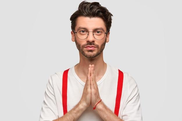자신감을 가지고 자신감을 가지고 수염을 기른 젊은 남성은 손을 잡고기도 제스처를 취하고 빨간색 중괄호가 달린 흰색 스웨터를 입고 심각한 얼굴을 가지고 있으며 더 잘 믿습니다. 매력적인 젊은 남자는 더 나은 믿음을 가지고