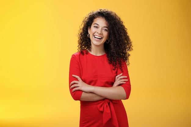 かわいい赤いドレスを着た自信に満ちた幸せな熱狂的な縮れ毛の女性レポーターは、気楽に笑い、頭を傾けて楽しんで、黄色い壁の上で自信を持ってポーズをとって体に手を組んで手をつないでいます。